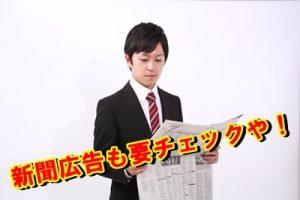 新聞で転職活動する男性